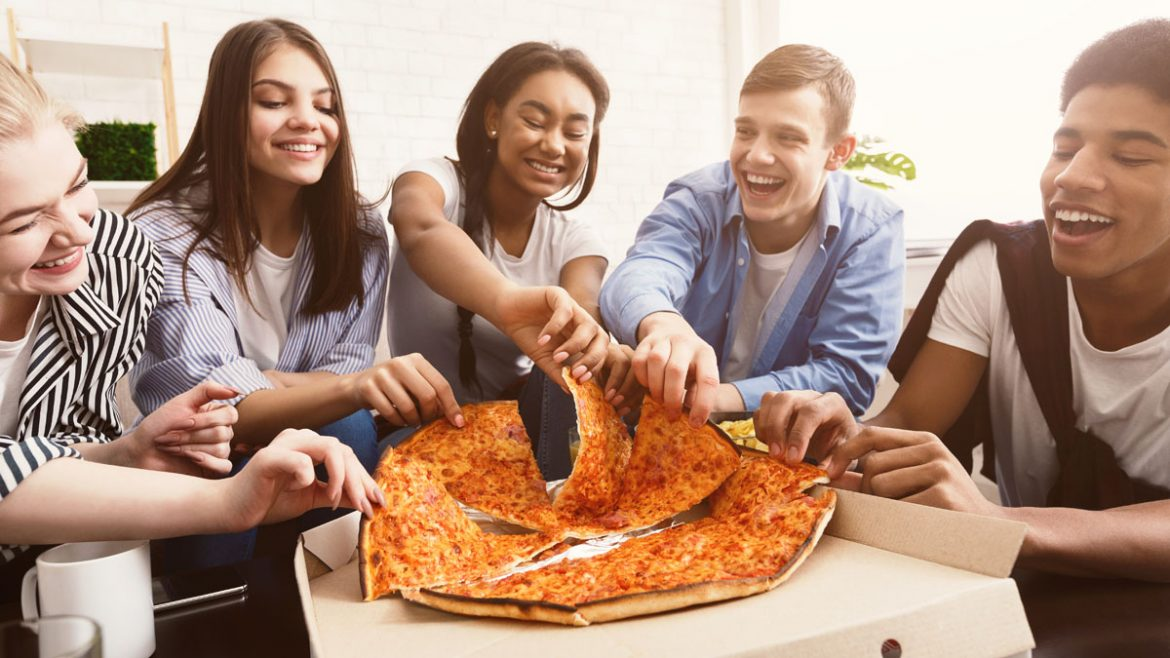 Time for snack. Happy students eating pizza and chatting
