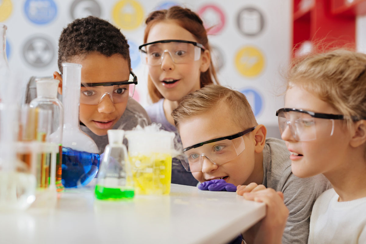 Group of classmates observing chemical reaction with awe